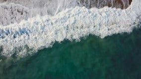 沙子海滩 股票 一个美丽的沙滩的顶视图与蓝色的挥动辗压入岸 背景峡湾光芒海运星期日 免版税库存图片