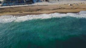 沙子海滩 股票 一个美丽的沙滩的顶视图与蓝色的挥动辗压入岸 背景峡湾光芒海运星期日 库存图片