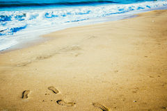 沙子海滩和海浪和脚步 免版税库存照片