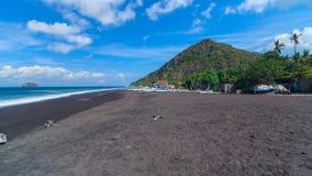 黑沙子海滩在巴厘岛海岛上的在印度尼西亚 免版税库存图片