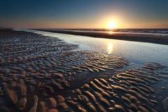 沙子海滩处于低潮中和日落 免版税图库摄影
