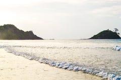 沙子海滩海在背景中挥动岩石,过滤银色云彩的太阳光芒 库存图片