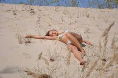 沙子海滩的俏丽的微笑的女孩 免版税图库摄影