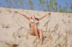 沙子海滩的俏丽的微笑的女孩 免版税库存照片