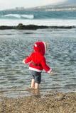 沙子海滩水的圣诞老人男孩 图库摄影