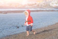 沙子海滩水的圣诞老人男孩 免版税库存图片