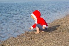沙子海滩水的圣诞老人男孩 免版税库存照片
