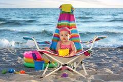 沙子海滩的女婴与玩具 库存图片