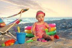 沙子海滩的女婴与玩具 免版税库存照片