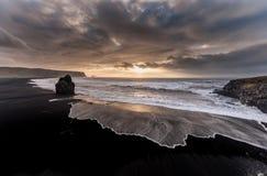 黑沙子海滩Reynisfjara在冰岛 有风早晨 重点前景海浪通知 五颜六色的天空 早晨日落 库存照片