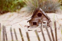 沙子的微小的海滩前的鸟房子 免版税图库摄影