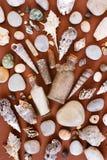 沙子的样式在玻璃瓶、海壳和石头的 免版税库存照片