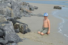 沙子的男孩沿在希尔顿黑德岛,南卡罗来纳的多岩石的海滩 库存照片