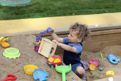 沙子箱子的卷曲男孩 免版税库存图片