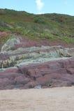 沙子,在海滩的红色岩石纵向视图  免版税库存照片