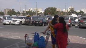 沙扎,阿拉伯联合酋长国- 2018年1月:有寻找他们的在停放的购物车的印地安妇女汽车在超级市场附近或 股票录像