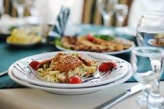 沙拉与在一块白色板材chiken 服务在与一张绿色桌布的一张桌上在餐馆 库存照片