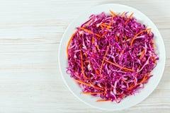 沙拉凉拌卷心菜-红叶卷心菜用在白色盘的红萝卜 免版税库存照片