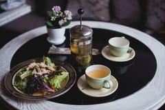沙拉和热的茶在桌上 免版税库存图片