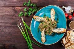 沙拉烘烤了茄子用葱、大蒜、草本、油煎方型小面包片和蕃茄在黑暗的木背景 在桌上的成份 库存照片