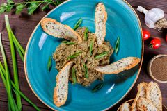 沙拉烘烤了茄子用葱、大蒜、草本、油煎方型小面包片和蕃茄在黑暗的木背景 免版税图库摄影