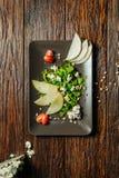 沙拉用乳酪和梨在板材在黑暗的木背景与地方文本的 鲜美的开胃菜 免版税库存照片
