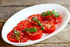 沙拉用切的蕃茄, rucola,芝麻籽 在一块白色板材的快的蕃茄沙拉在老木背景 免版税库存图片