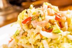 沙拉用圆白菜、虾和鲕梨在白色板材 库存图片