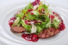 沙拉用小牛肉烤了,新鲜的莴苣和芝麻菜,在白色圆的板材的糖醋樱桃调味汁 图库摄影