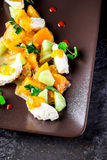 沙拉用山羊乳干酪和蜜桔在棕色板材 免版税库存图片