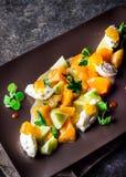 沙拉用山羊乳干酪和蜜桔在棕色板材 库存图片