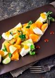 沙拉用山羊乳干酪和蜜桔在棕色板材 库存照片