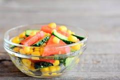 沙拉用新鲜的蕃茄、黄瓜和罐装玉米穿戴了与橄榄油和柠檬汁 在碗的菜沙拉 免版税图库摄影