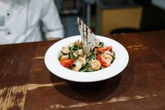 沙拉用海鲜和菜在一块板材在一张木桌的背景 免版税库存图片