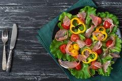 沙拉用烟肉和菜在一块板材在一块绿色餐巾 库存图片