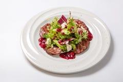 沙拉用烤小牛肉和新鲜的沙拉在一块白色板材离开 免版税库存照片