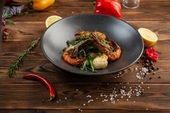沙拉用烤虾和酥脆菜在一块板材在木背景 库存照片