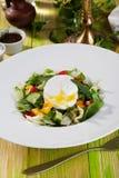沙拉用荷包蛋,黄瓜,芝麻菜,圆白菜,胡椒,在木桌绿色黑板俏丽的食物的静物画 库存照片