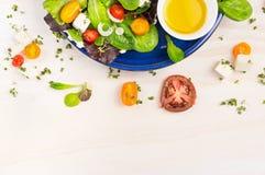 沙拉用蕃茄、希腊白软干酪和油醋在蓝色板材在白色木背景 图库摄影