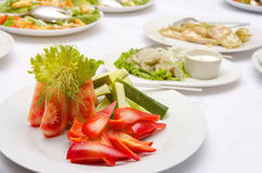 沙拉用蕃茄、胡椒和黄瓜在白色板材 免版税库存图片