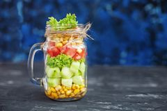沙拉用蕃茄和玉米和黄瓜和莴苣 蓝色bac 免版税库存图片