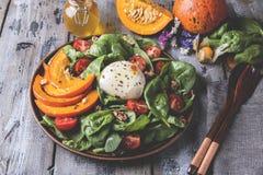 沙拉用被烘烤的南瓜,无盐干酪乳酪,菠菜绿化,在一块板材的蕃茄在一张木桌上 免版税库存图片