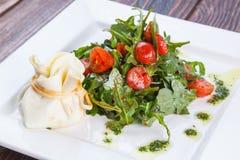 沙拉用西红柿和芝麻菜用乳酪请求 图库摄影