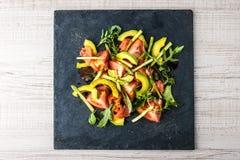 沙拉用鲕梨、鳟鱼和芦笋在黑石顶视图 免版税库存图片