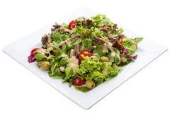 沙拉用鲥鱼和菜在一块白色板材 免版税库存照片