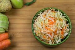 沙拉由切好的菜、红萝卜、圆白菜、芹菜和撇蓝制成在绿色盘在鳕鱼板 免版税库存图片