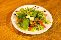 沙拉的侧视图包括了荷兰芹、egss、蕃茄、肉和芝麻菜和装饰用棕色沙司 库存照片