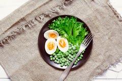 沙拉的有机成份用莴苣、结冰的豌豆和鸡蛋在土气背景 健康食物或者饮食营养 库存照片