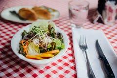 沙拉盘包括黄瓜,蕃茄,莴苣,圆白菜,红萝卜,赤栎,青葱,狂放的火箭顶部用无盐干酪乳酪 免版税库存照片