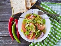 沙拉青豆,蕃茄,在一个木食家莴苣的营养,在开胃的红辣椒上添面包 库存图片